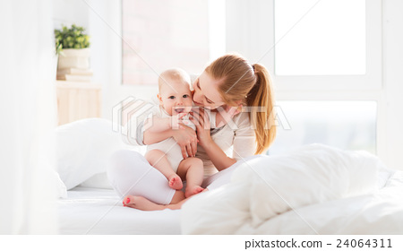 happy family mother  with baby playing and hug in bed 24064311