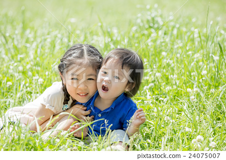 My older sister and brother playing in a fresh green park 24075007