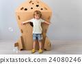 Little boy standing near carton rocket 24080246