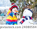 Funny kid boy in colorful clothes making a snowman 24080564