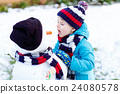 Funny kid boy in colorful clothes making a snowman 24080578