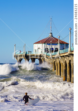 A surfer challenging Manhattan Beach's jetty and big wave 24083215