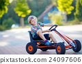 little kid boy driving pedal race car in summer 24097606