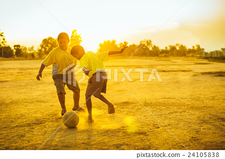 The boys are playing football in the sunshine day. 24105838