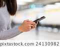 Woman use of mobile phone at train station 24130982