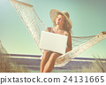 Beautiful Woman Sitting on a Hammock by the Beach 24131665