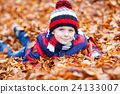 Cute little kid boy on autumn leaves background in 24133007