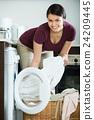 Young woman near washing machine 24209445