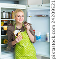 Woman eating chocolate from fridge 24209521