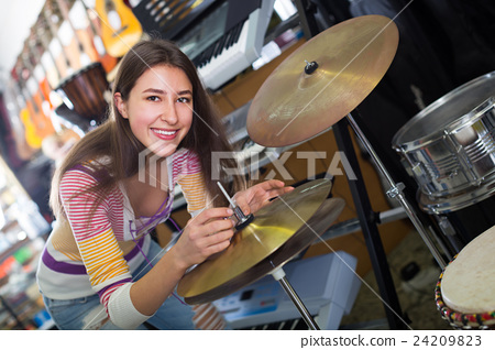 Young girl selecting drums and accessories 24209823