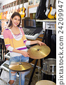 Adult girl selecting drums and accessories 24209947