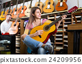 customers in music instruments shop 24209956