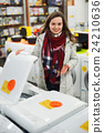 Positive young female customer looking at dryers 24210636