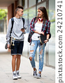 Teenage friends carrying skateboards in the city 24210741