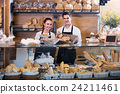 Adult man and girl selling pastry and loaves 24211461