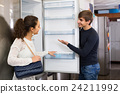 family couple choosing new refrigerator in hypermarket 24211992