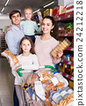 parents with two kids choosing biscuits in store 24212218