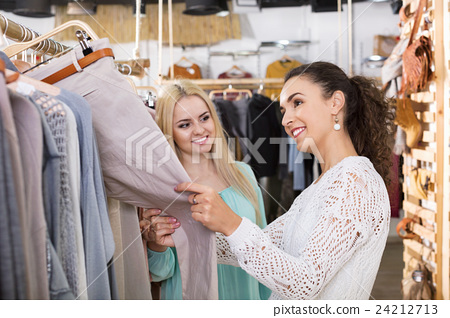 Happy young female friends choosing trousers 24212713
