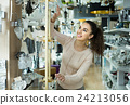 Ordinary woman doing shopping in lighting shop 24213056