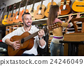 customers in music instruments shop 24246049