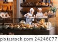 Bakery staff offering bread 24246077