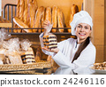 Portrait of friendly smiling woman at bakery display 24246116