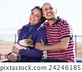Mature couple with a small dog outdoors. 24246185