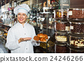Smiling positive seller with dark and white chocolates confectionery 24246266