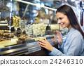 Smiling girl choosing chocolates. 24246310