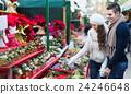 Couple buying Christmas flower at market 24246648