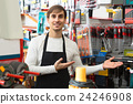 male seller posing at tooling section of household store 24246908