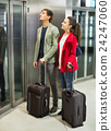Positive young people with luggage standing 24247060