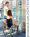 Couple with wheelchair in elevator 24247353