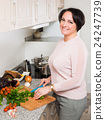 Positive housewife cooking veggies at home 24247739