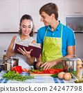 Couple at kitchen with vegetables at the table. 24247798