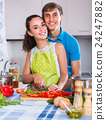 Couple at kitchen with vegetables at the table. 24247882