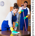 Cleaners in overalls with supplies working indoors 24266191