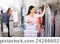 Woman choosing pajamas in lingerie shop 24266602