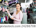 female customer holding different pair of socks in hands in underwear store 24266708