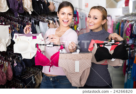 5cf95a4484 two female customers holding bras and panties in hands in underwear store