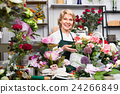 Female florist wearing an apron and happily standing among flowers 24266849