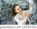 Woman choosing interior lights in mall. 24267435
