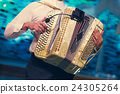 The musician playing the accordion 24305264