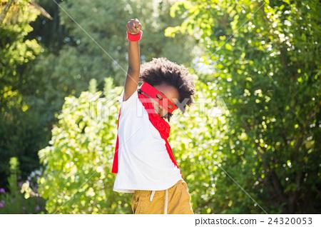 Boy dressed as a super hero in a park 24320053