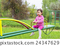 Little cute girl sits on seesaw in a sunny day 24347629