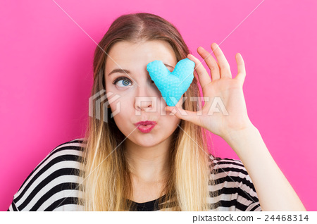 A woman with a small heart cushion 24468314