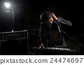 Musician playing keyboard with music instrument and lens flare from spot light on dark background, Musician concept 24474697