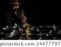 A saxophone player in a dark background with music melody, musical concept 24477797