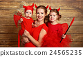 happy family with costumes devil prepares for Halloween 24565235