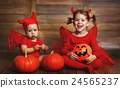 children are devil costume with pumpkins prepared for Halloween 24565237